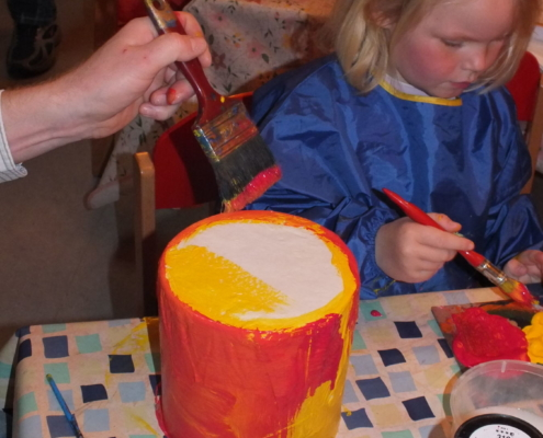 Kind bemalt eine Papprohrtrommel